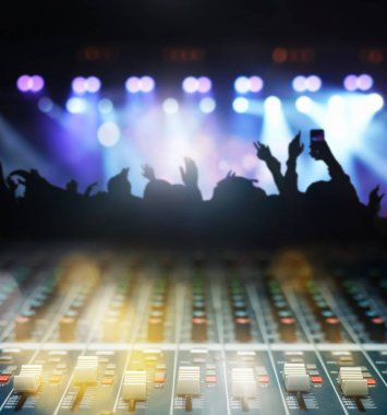 Closeup up hands the sound mixer over the photo blurred of Concert crowd in silhouettes of Music fanclub follow up the songer at the front of stage with follow light