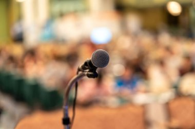 Microphone over the Abstract blurred photo of conference hall or seminar room with audience background, education and learning concept