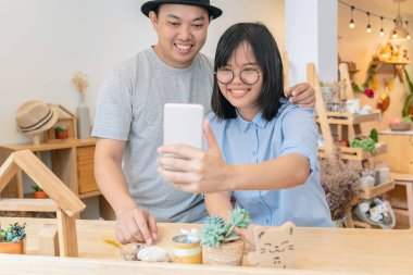 Asian Young Couple taking the selfie with happiness action in modern coffee shop or workplace or co-working space or modern office, lifestyle and leisure concept