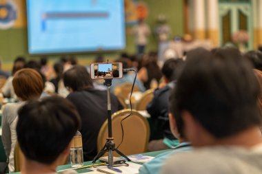 Closeup smart mobile phone taking Live streaming with audience to Asian Speaker with casual suit standing and giving the knowledge on the stage in the conference hall or seminar meeting, business and education concept
