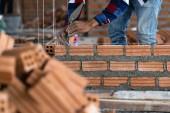 Fotografie Detailní ruční profesionální stavební dělník zdění do nové průmyslové lokality. vytvořit koncepci průmyslu a zdiva