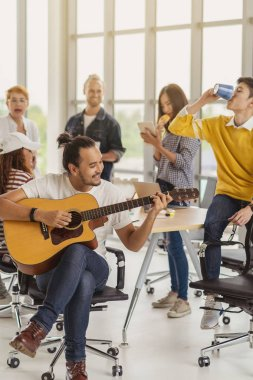 Asian worker playing the guitar over the Group Of Asian and Multiethnic Business people with casual suit talking and eatting with happy action when lunch time in the creative office workplace, life style and relax work concept