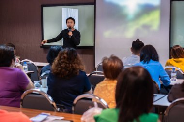 Asian Speaker or lecture with casual suit on the stage in front of the room presenting with the screen in the conference hall or seminar meeting room, business and education concept