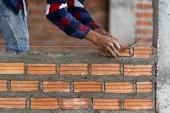 Detailní ruční profesionální stavební dělník zdění do nové průmyslové lokality. vytvořit koncepci průmyslu a zdiva