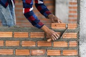 Fotografia Operaio di costruzione professionale di mano closeup posa mattoni nel nuovo sito industriale. costruire il concetto di industria e muratura