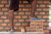 Fotografie Closeup Bein der professionelle Bauarbeiter verlegen der Ziegel im neuen Industriegebiet. Industrie und Mauerwerk Konzept zu konstruieren