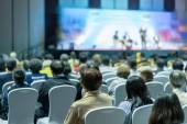 Pohled zezadu na publikum poslechu reproduktory na pódium v konferenční sál nebo seminář setkání, podnikání a vzdělávání o složení investic