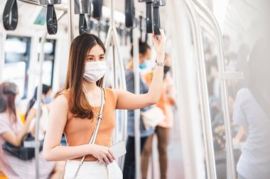 Young Asian woman passenger wearing surgical mask and listening music via smart mobile phone in subway train when traveling in big city at Covid19 outbreak, Infection and Pandemic concep