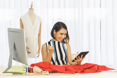 Young Asian Designer woman working and using the technology tablet at workplace over Clothes mannequins, small business startup, Business owner entrepreneur, modern freelance job lifestyle concept