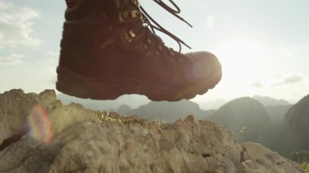 Slow Motion Close Up Detail Of Vintage Leather Mountaineering Boots Unrecognizable Adventurous Female Hiker Leaving The Peak And Walking Downhill On Beautiful Sunny Summer Day In European Alps