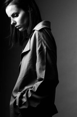 beautiful young girl in a trench coat, black and white