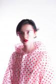 Frau im Regenmantel mit roten Tupfen, durchsichtiger Schutzbrille, seltsam modischem Stil
