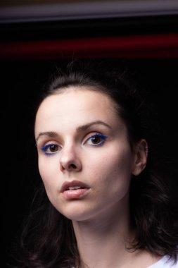 woman with blue eye makeup, portrait close-up, black background