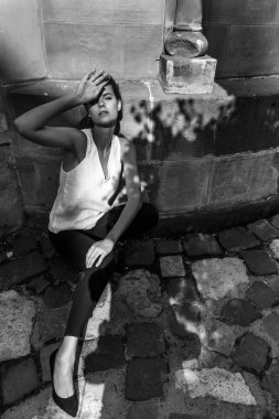Woman in a white T-shirt standing on the street, shading her face from the sun with shadows.