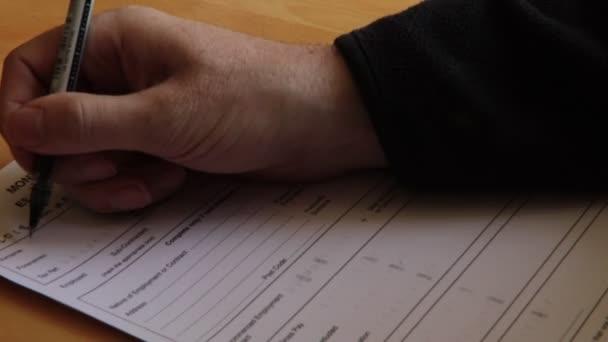 Hand mit Füllung eines Formulars auf dem Schreibtisch