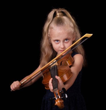 Happy little blond girl learns to play the violin isolated on black background