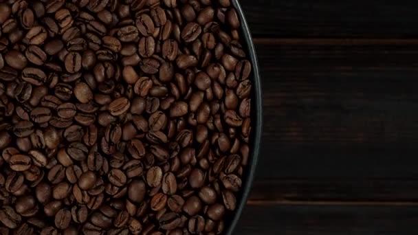 pörkölt kávébab fekete tányérral forgó felülnézetben. sötét fa háttér. a szöveg helye