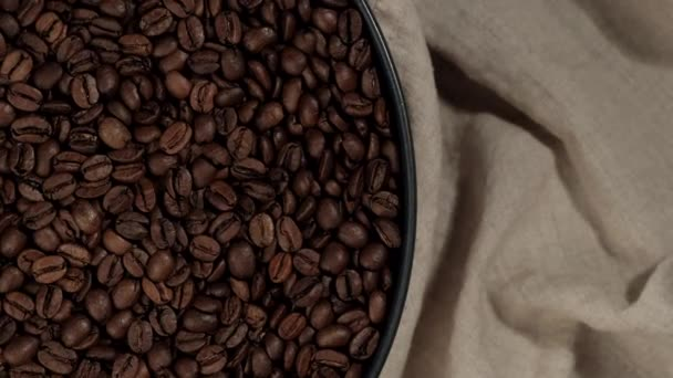 roasted coffee beans in black plate and on beige linen cloth top view rotating
