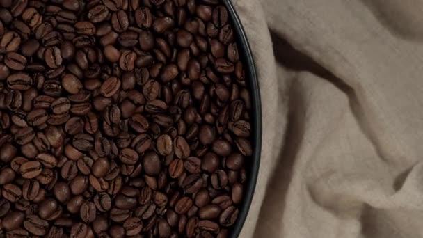 pražená kávová zrna v černé desce a na béžovém plátně vrchní pohled rotující