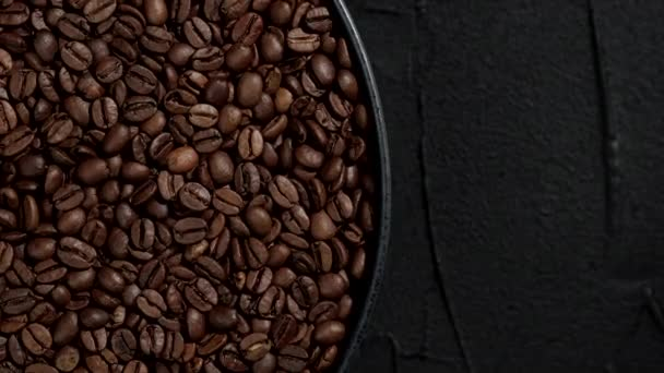roasted coffee beans in black plate rotating top view. black background. place for text
