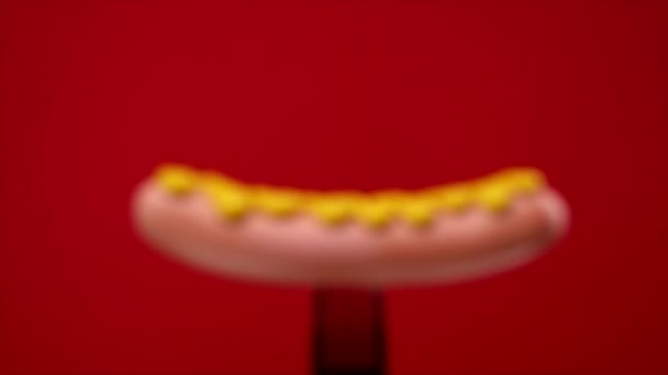 sausages. pouring mustard on hot sausage. sausage on black fork red background. the camera zooms in on the subject