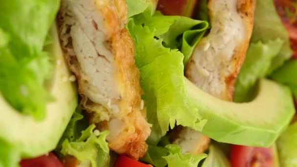 chicken salad with avocado, tomatoes, lettuce, sesame seeds rotating. Healthy salad with chicken. vertical video