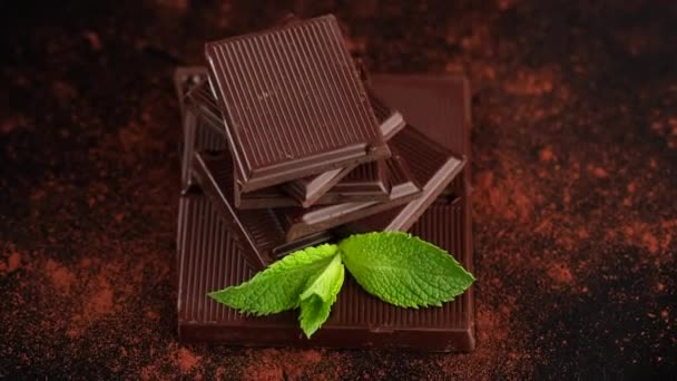 čokoláda. tmavá čokoládová tyčinka a kakao prášek s mátovým listem rotující horní pohled. Cukrárna, koncepce cukrovinek.