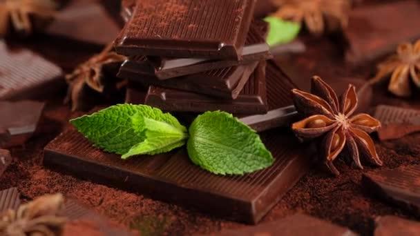 čokoláda. tmavá čokoládová tyčinka a kakaový prášek s mátovým listem rotující. Cukrárna, koncepce cukrovinek.
