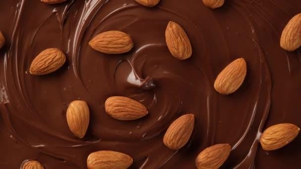 tavená prémiová čokoláda rotující s ořechy mandle, pohled shora