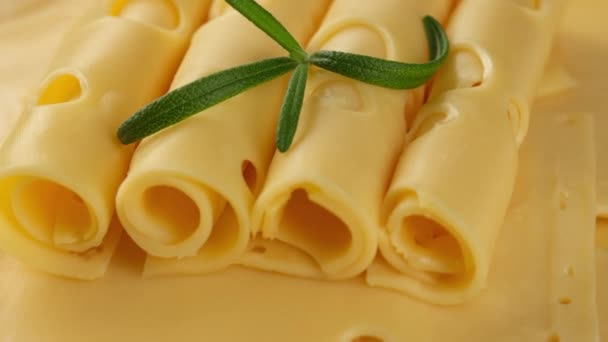 gold Netherlands or Swiss cheese with rosemary leaf rotating
