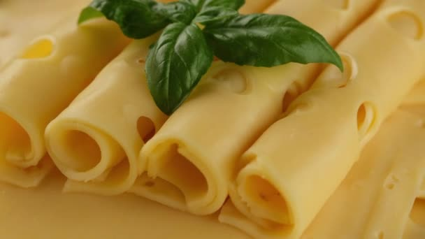 gold Netherlands or Swiss cheese with basil leaf rotating