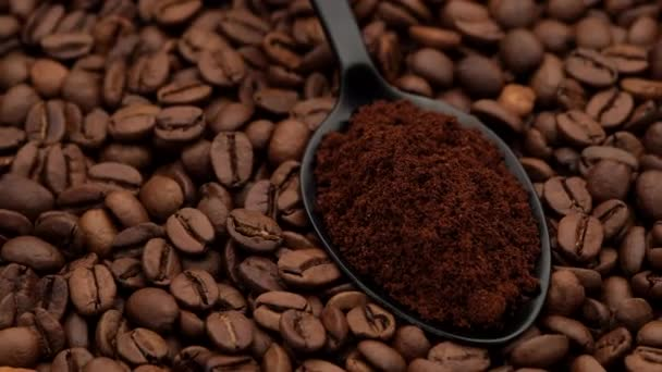 ground coffee in black spoon and coffee beans on background rotation to left