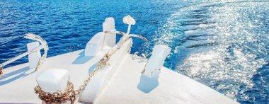Wide cut closeup shot of a white yacht on clear blue sea