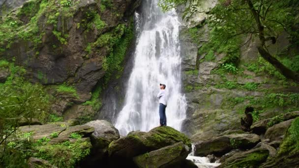Man relaxing with freedom beautiful waterfall in the national park forest at Khlong Lan Waterfall, Kamphaeng Phet Thailand