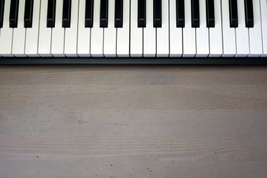 Music keyboard on brown wooden background close up view with free space for your text