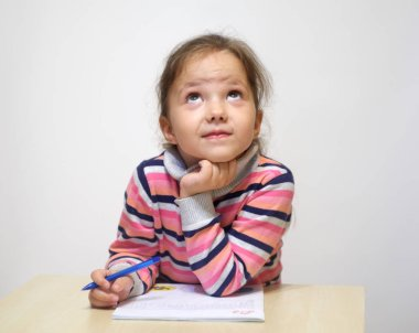 The adorable little girl doing homework and dreams.