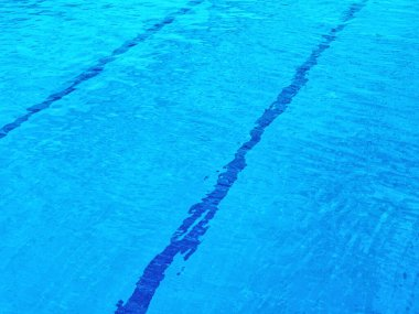 Pool with clear blue water. At the bottom of the pool, parallel lines are visible that cross the background diagonally