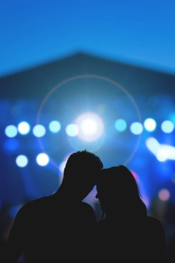 Young couple silhouettes enjoying on the concert.