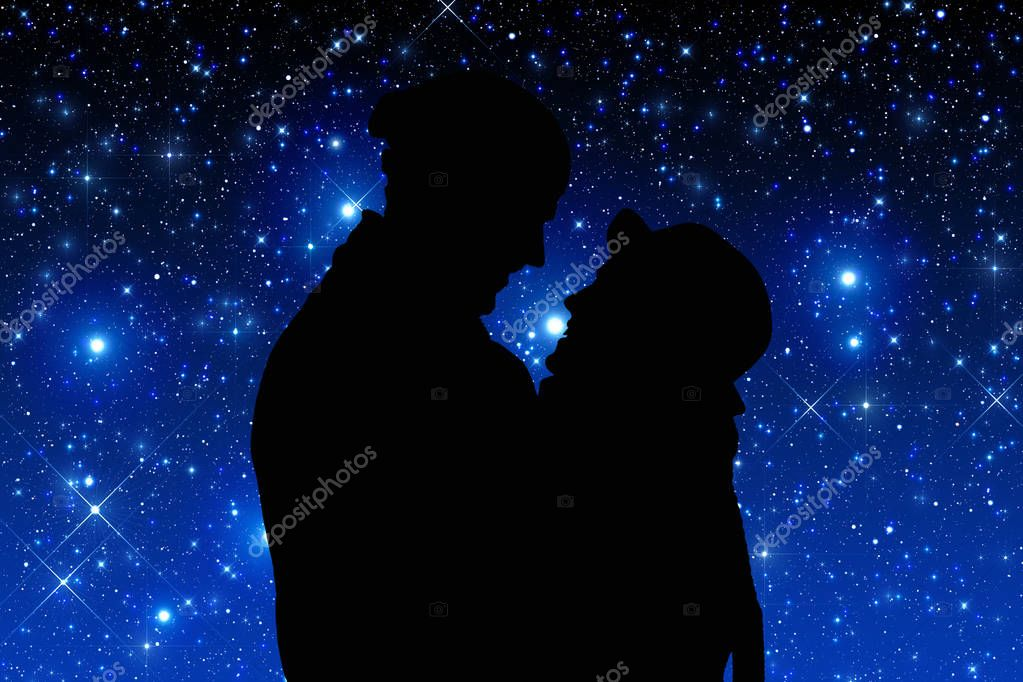 Silhouettes of a young couple under the starry sky.