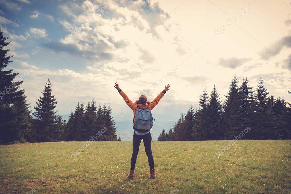 Woman with wide opened arms enjoying in the nature and feeling free.