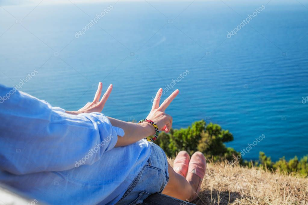 Girl enjoying the ocean / sea and holding two finger - peace symbol.