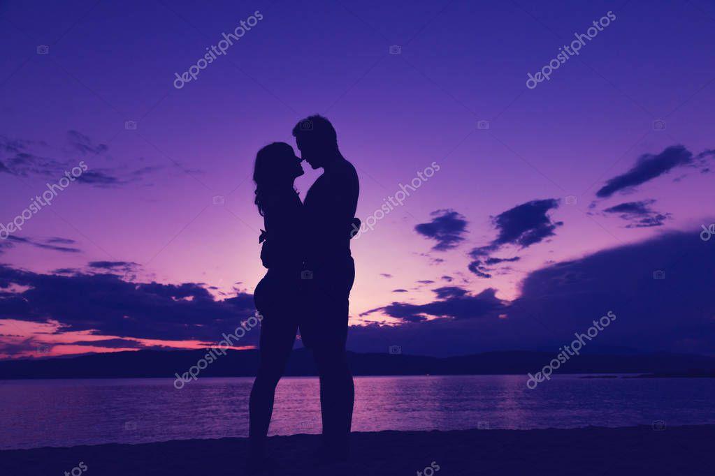 Couple enjoying on the beach in sunset / sunrise time.