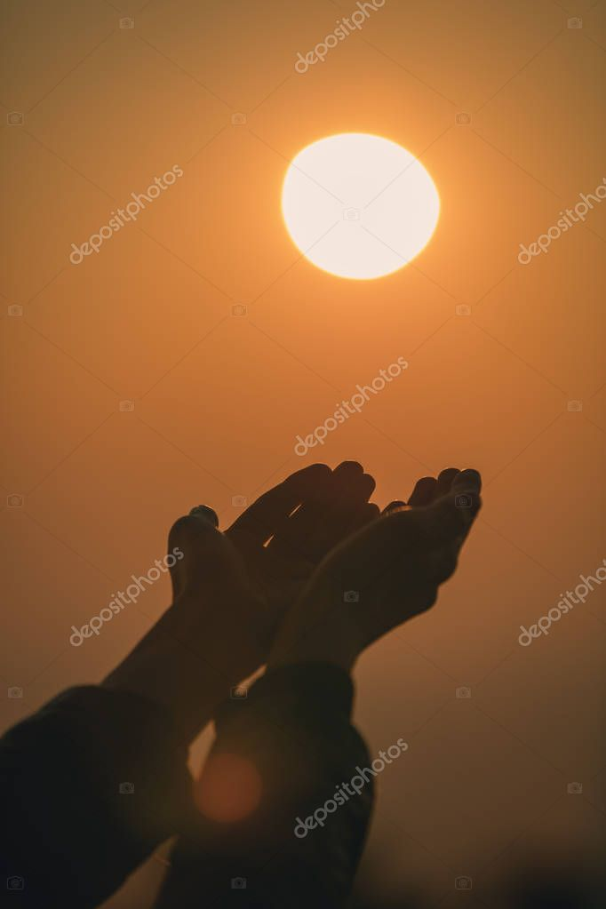 Praying hands of girl in sunset / sunrise with sea / ocean backround.