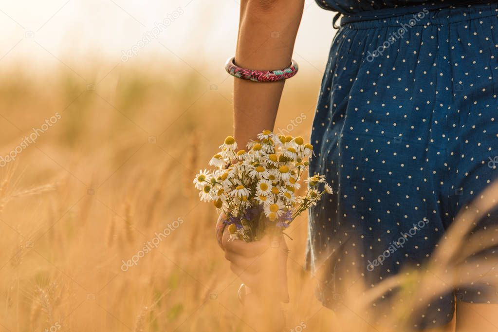 Girl in a wheat-field with bouquet of flowers.