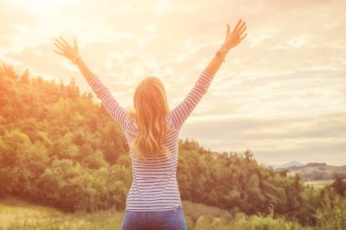 Woman enjoying in the nature with arms wide open.