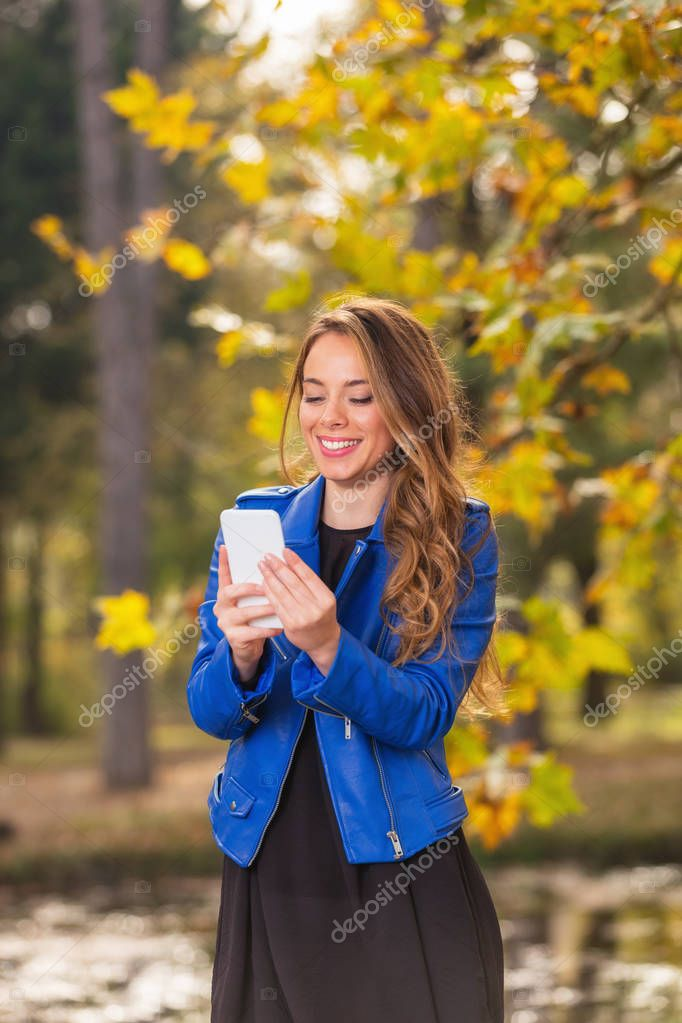 Young girl using cellphone in the park with autumn / fall colors.