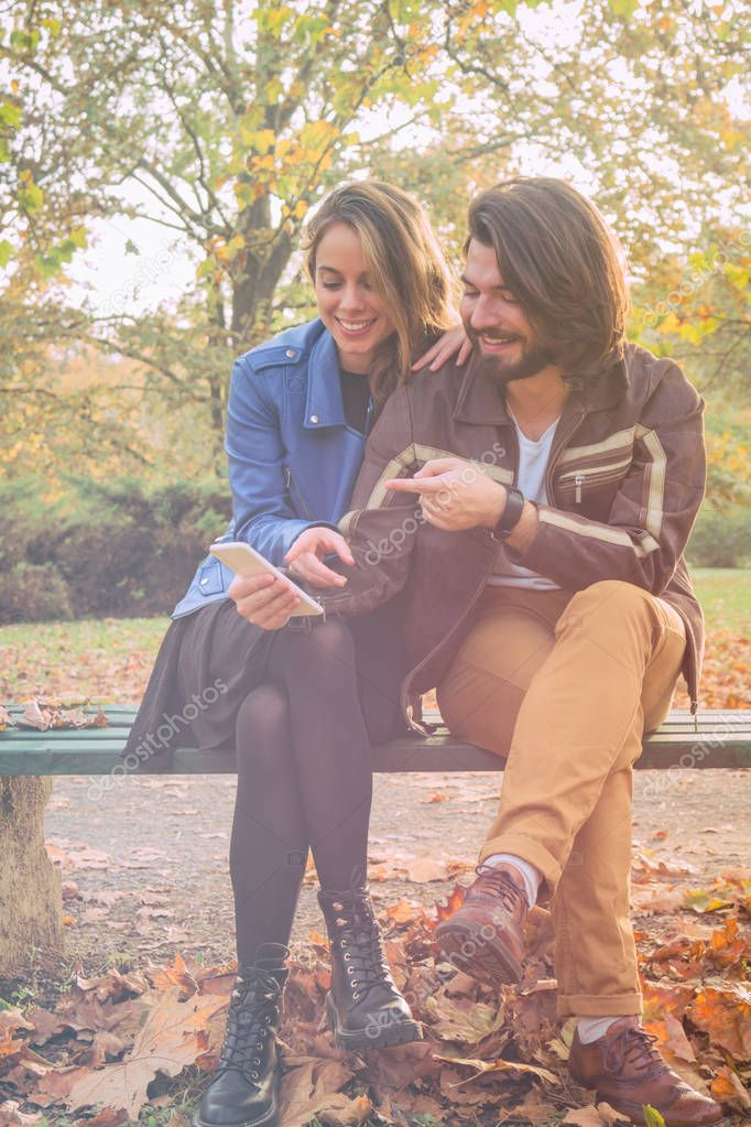Cute couple making selfie on a bench in the park at autumn / fall season.