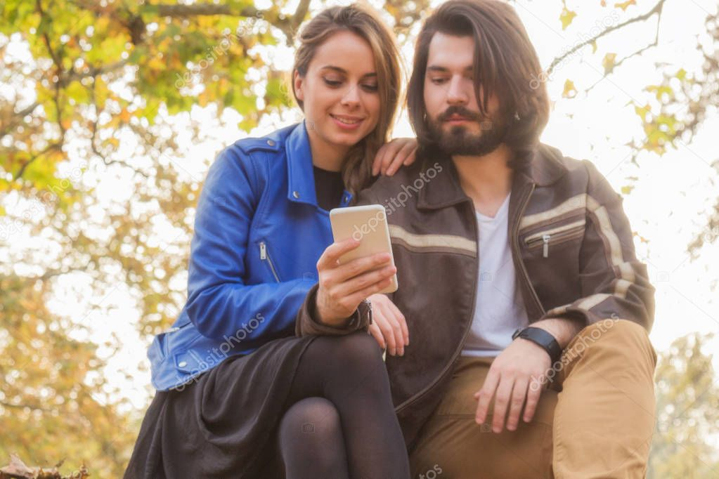 Cute couple making selfie on a bench in the park at autumn / fall season. Optical focus is on the phone.