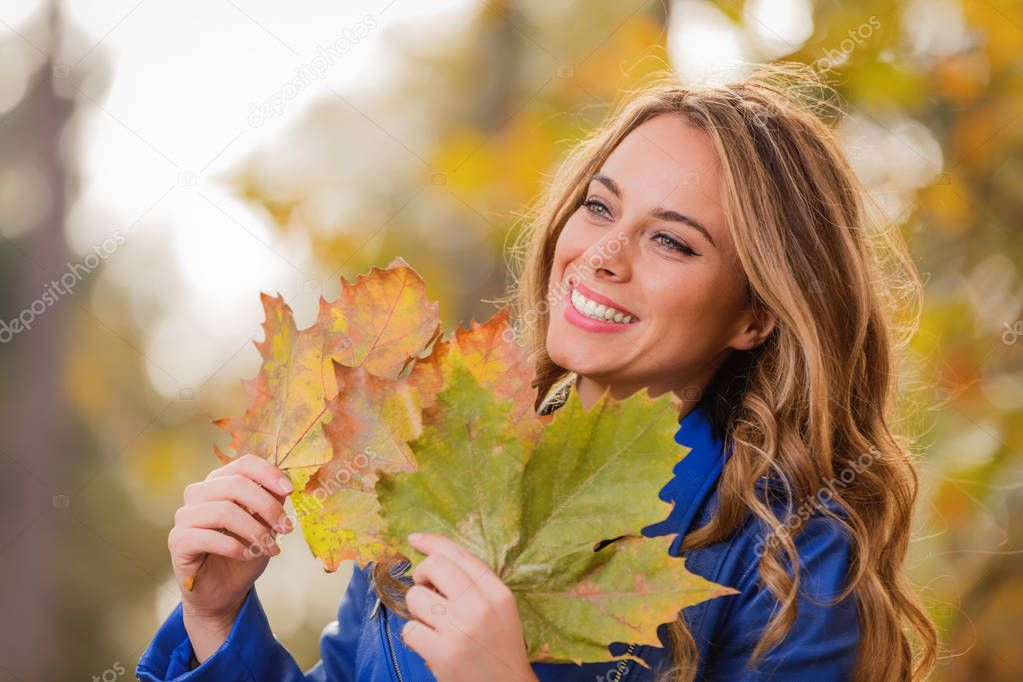 Cute smiley girl holding leaves in the nature.