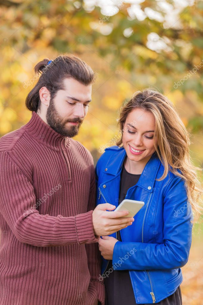 Cute couple making selfie in the park at autumn / fall season.